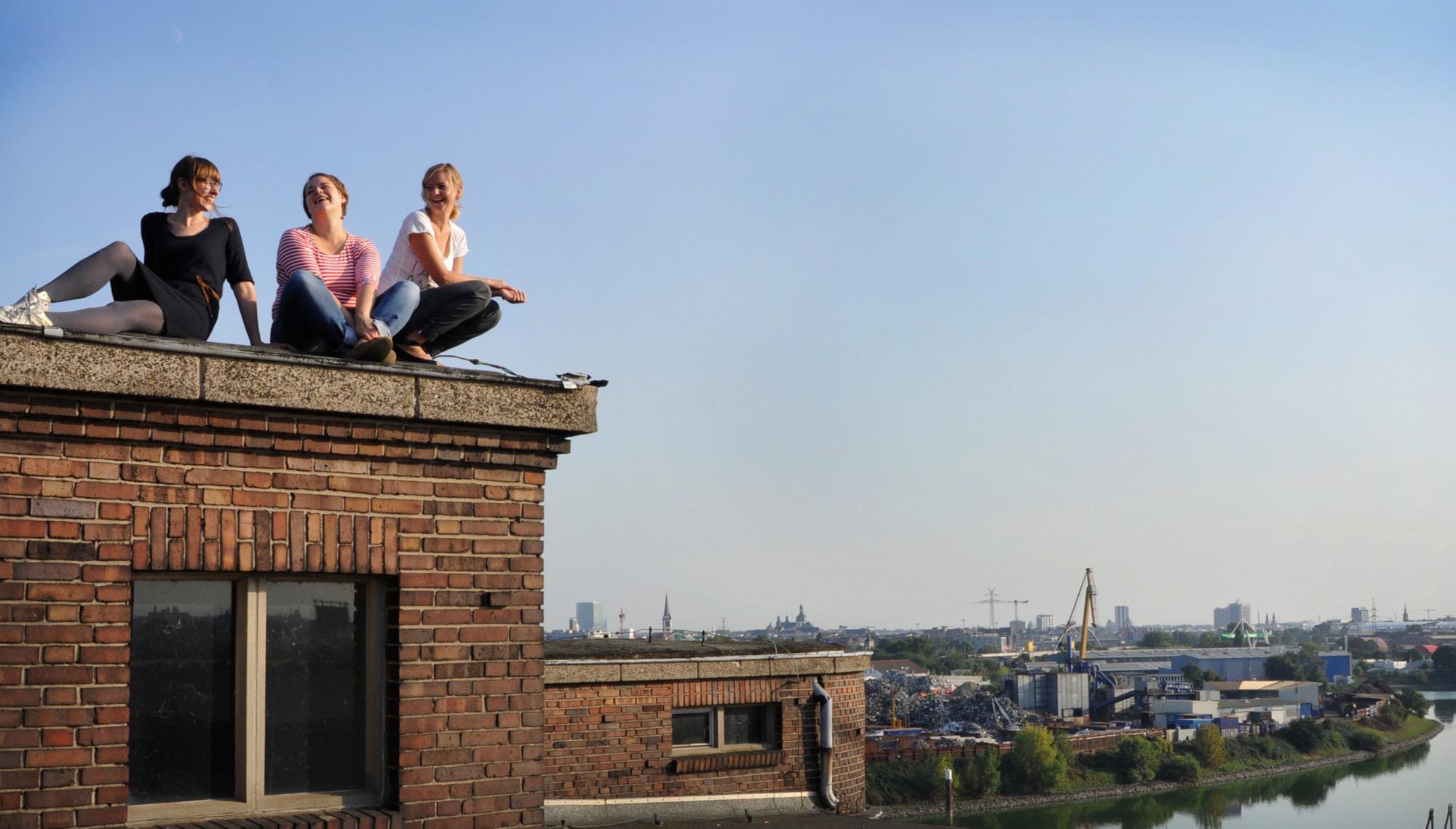 Die Gründerinnen Annika Wind, Anne Jeschke und Sarah Weik sitzen auf einem Dach über der Stadt.