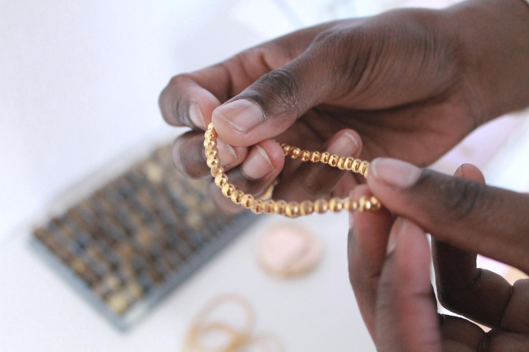 Anusiya hält ein Armband mit goldenen Perlen.