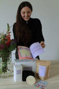 Clara zeigt stolz die Produktinformationen zu ihren Wochenbett Produkten.